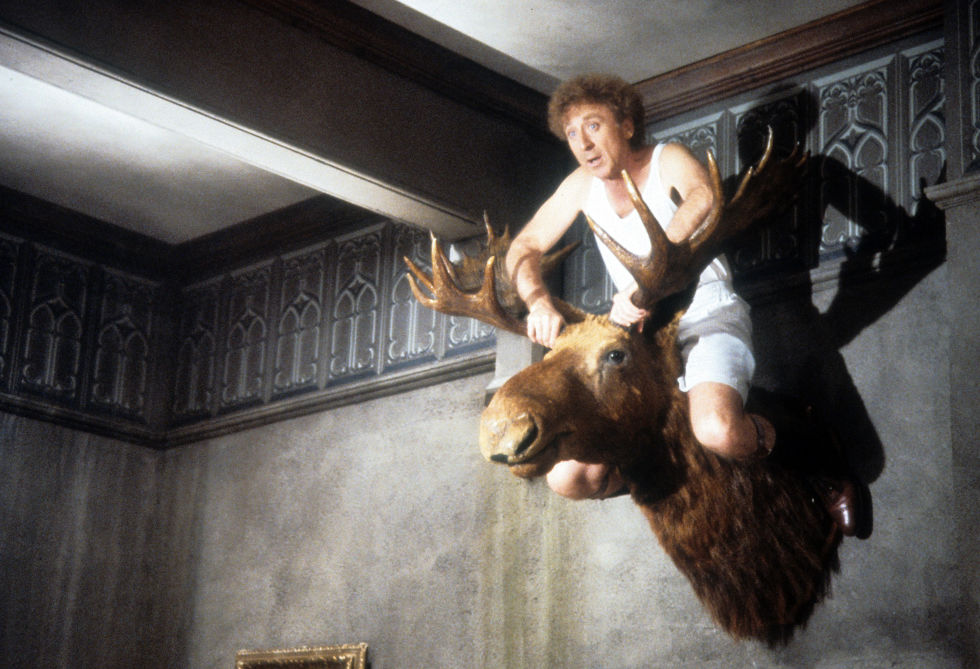 Gene Wilder sit atop a mounted moose head in a scene from the film 'Haunted Honeymoon', 1986. (Photo by Orion/Getty Images)