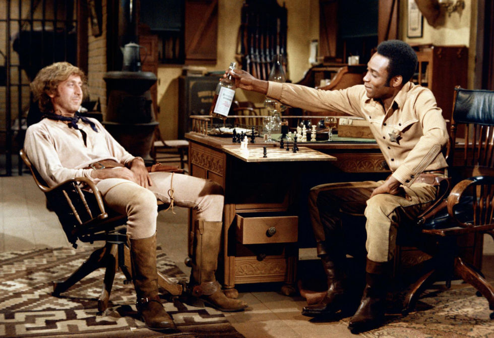 Full shot of Cleavon Little as Bart offering whiskey bottle for Gene Wilder as Jim, both seated in sheriff's office.
